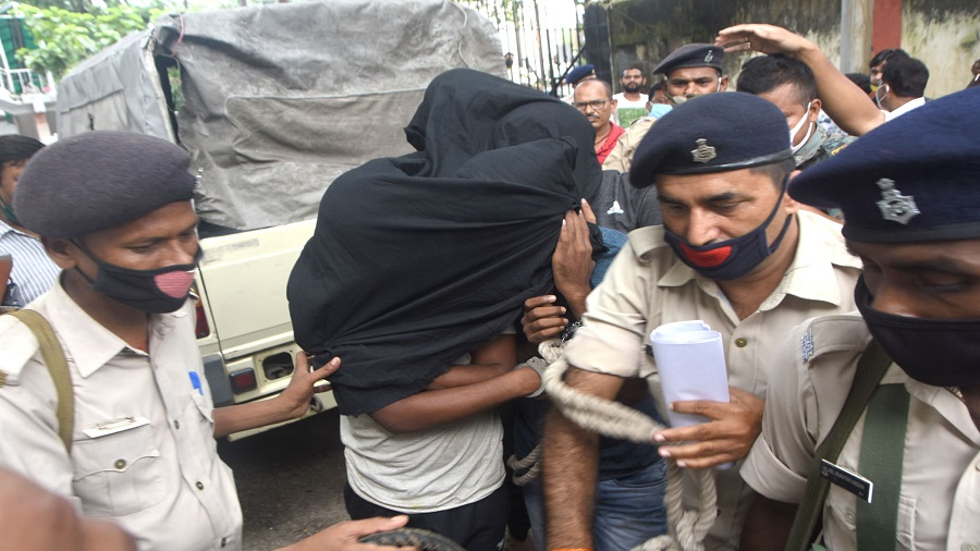 Four cyber criminals being taken to Dhanbad SP (city) R. Ramkumar's office in Dhanbad on Friday.