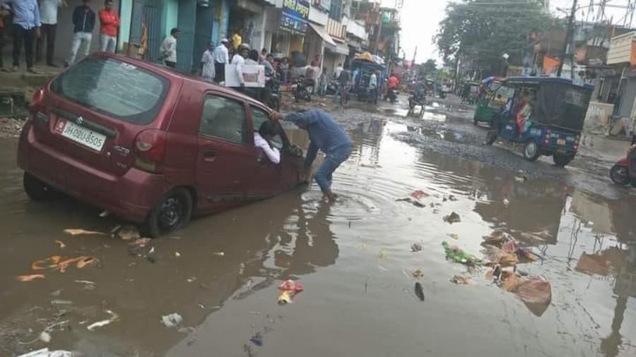A car negotiates craters on Hazaribagh Main Road (NH100).