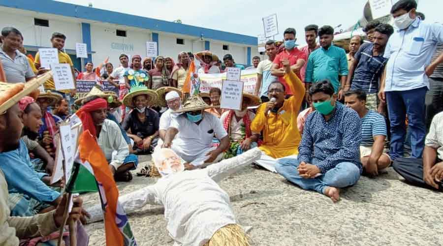 Farmers ready to burn an effigy of Narendra Modi during a protest organised by Trinamul at Bongaon on Friday