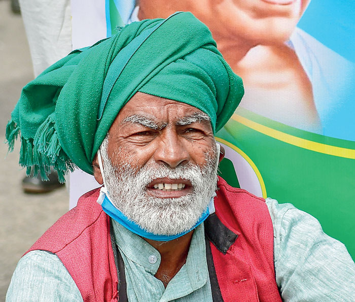 A farmer listens to a speech during a protest against the bills in Bangalore on Friday.