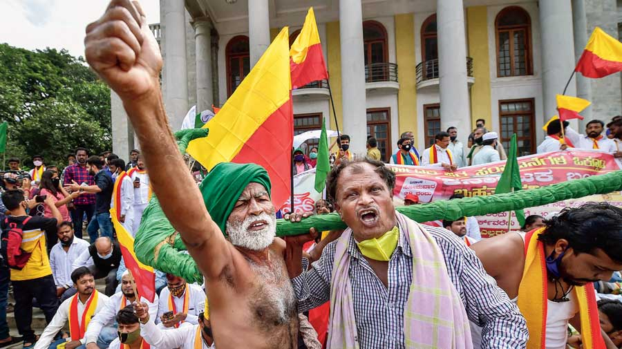 Members of various organisations along with farmers raise slogans at a protest against the farm bills in Bangalore on Monday.