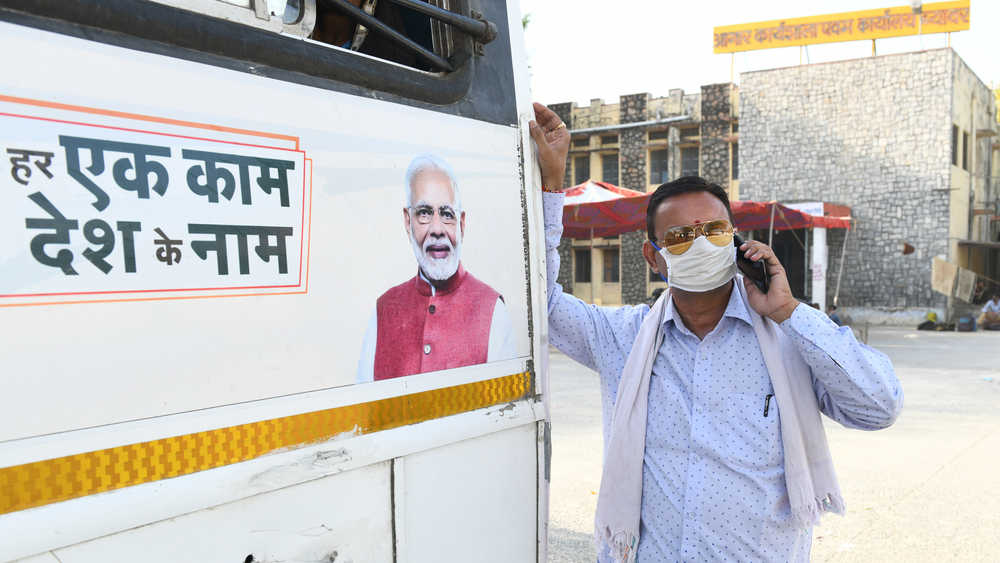 A roadways worker stands near a poster of Narendra Modi at a bus stand in Beawar, Rajasthan.