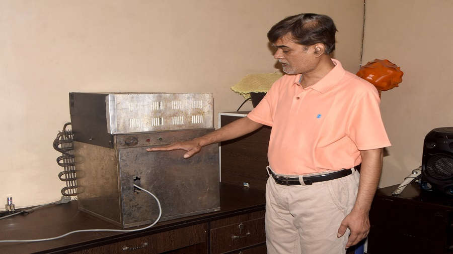Uday Thakur with his new creation, an 'atmospheric water generator' at his residence in Dhanbad on Wednesday