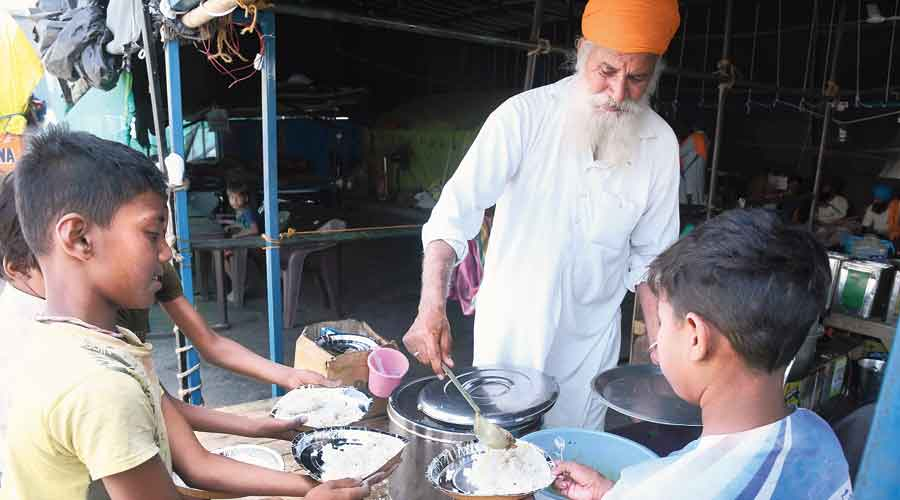 A protesting farmer serves food at a langar at the  Delhi-Ghazipur border on Wednesday.