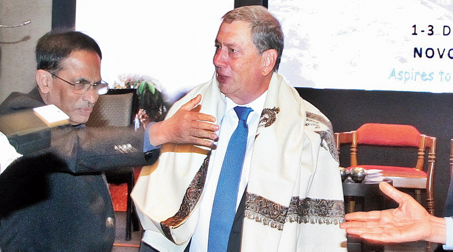 Former Gilead Sciences boss John C Martin felicitated with a shawl after delivering a speech in the city in 2016