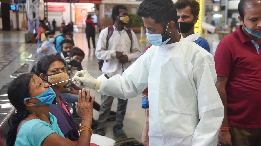 A health worker collects nasal sample from a passenger for COVID-19 test, at the Chhatrapati Shivaji Maharaj terminus in Mumbai on Saturday.