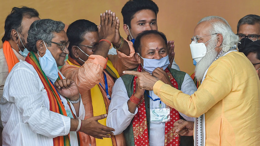 Prime Minister Narendra Modi interacts with party candidate Swapan Dasgupta during an election rally in support of his party candidates ahead of the third phase of state assembly polls, in Hooghly district on Saturday.