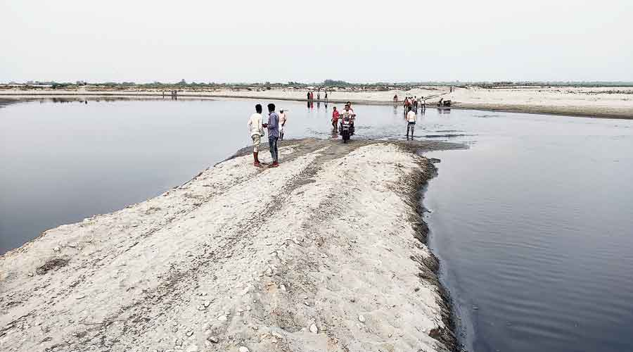 Voters returning home by crossing the Beki river in the Guileza area under Jania constituency of Assam's Barpeta district on Tuesday.