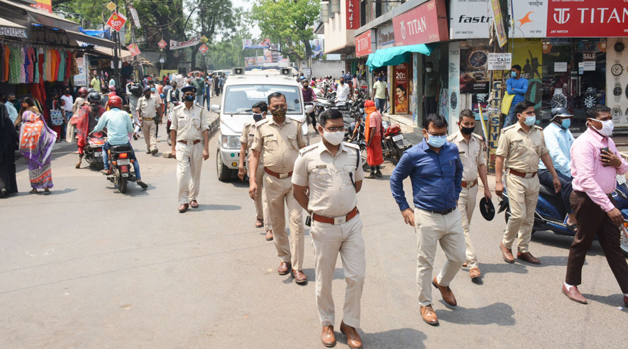 Police and JNAC officials patrol shops at Sakchi market on Wednesday.