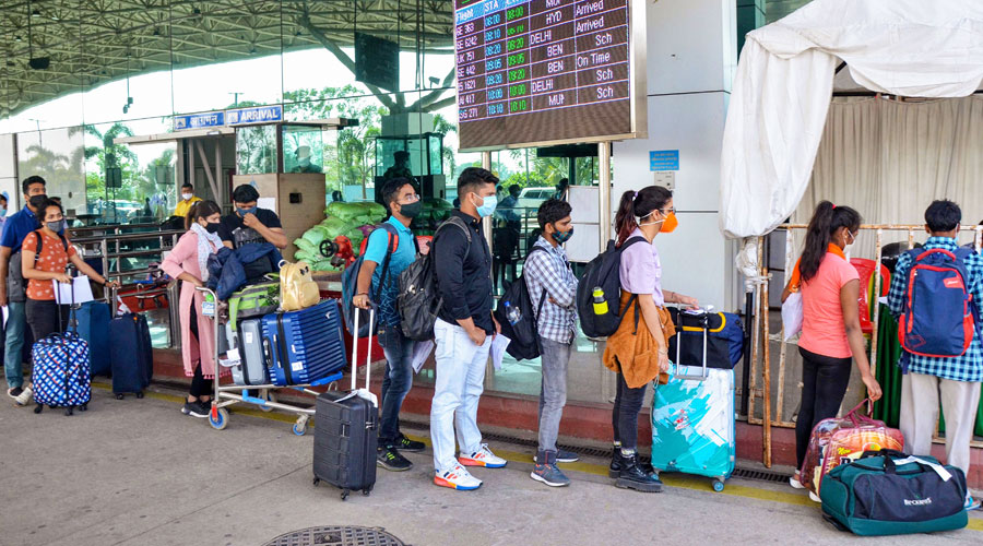Passengers stand in a queue at Birsa Munda International Airport to give their swab samples for Covid-19 tests, amid spike in coronavirus cases, in Ranchi on Monday, April 5, 2021.