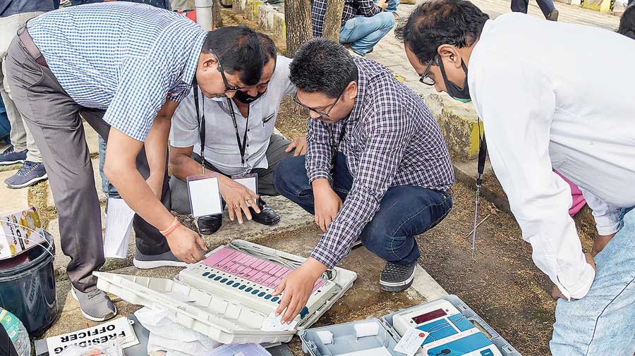 Polling officials check electronic voting machines and other items at a distribution centre in Kamrup district of Assam on Monday before the third and final phase of Assembly polls on Tuesday.