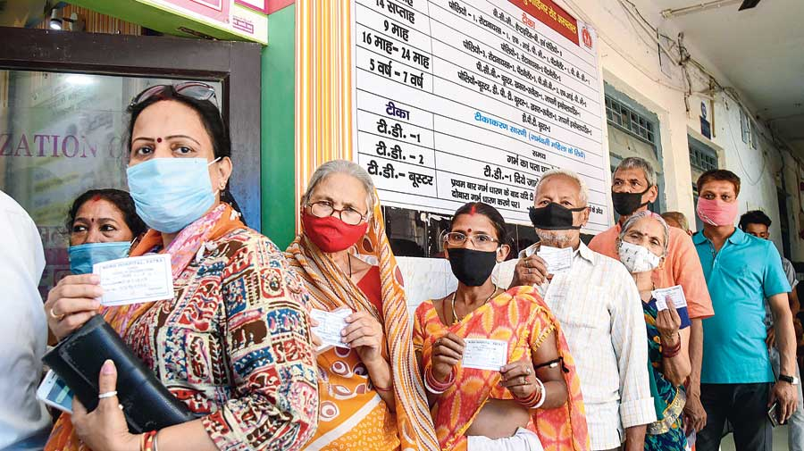 People stand in a queue as they wait for their turn to get vaccinated  at a dispensary in Patna on Wednesday.