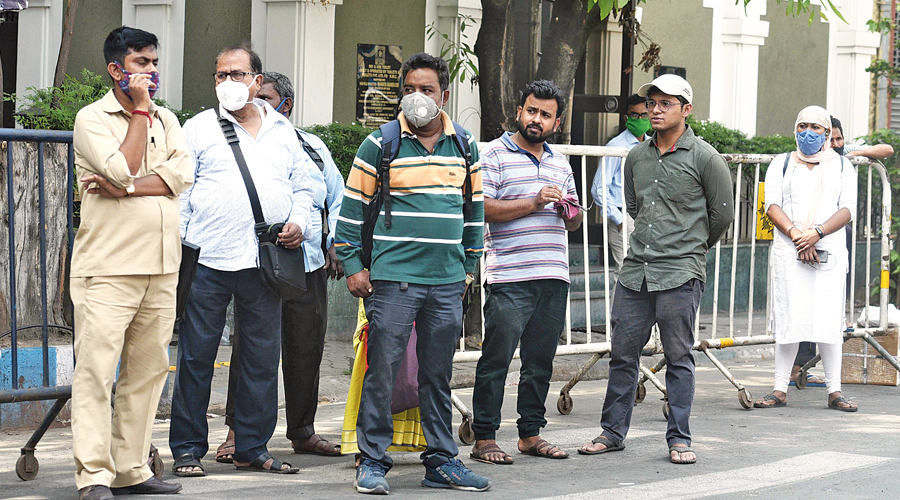 Commuters, some without masks, wait at a bus stop at the Exide crossing on Wednesday.