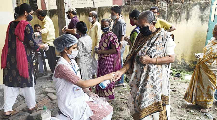 Aparajita Chatterjee gets her hands sanitised at a polling booth in Behala West  on Saturday