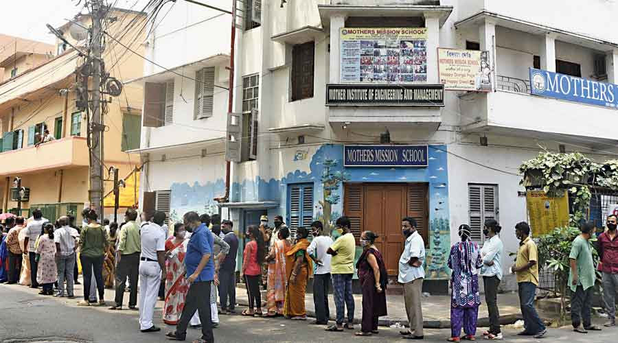 Voters queue up out side a polling booth in Behala West on Saturday morning