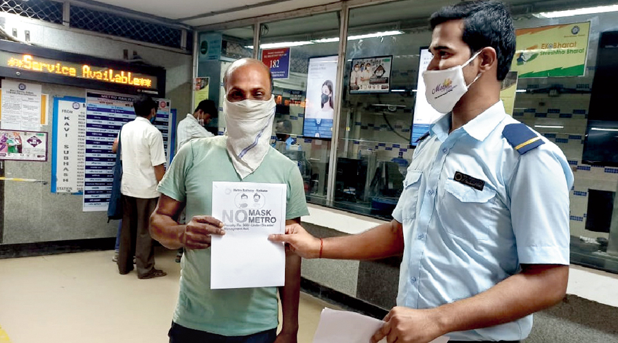 """Metro officials talk to passengers during a """"mask awareness drive"""" at New Garia station earlier this week"""