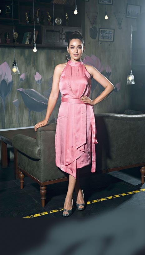 """Priyanka cuts a pretty picture in the soft pink georgette halter-neck dress styled with asymmetrical pleats and a belt around the waist. The hair pulled up into a neat bun, a shade of pink on the eyes and light pink lips, with simple hoops as accessory make the look apt for the summer months. """"This is a perfect summer outfit with minimal pleats in front, comfortable and absolutely trendy, adding charm and sophistication to your style quotient,"""" says Jyotee."""