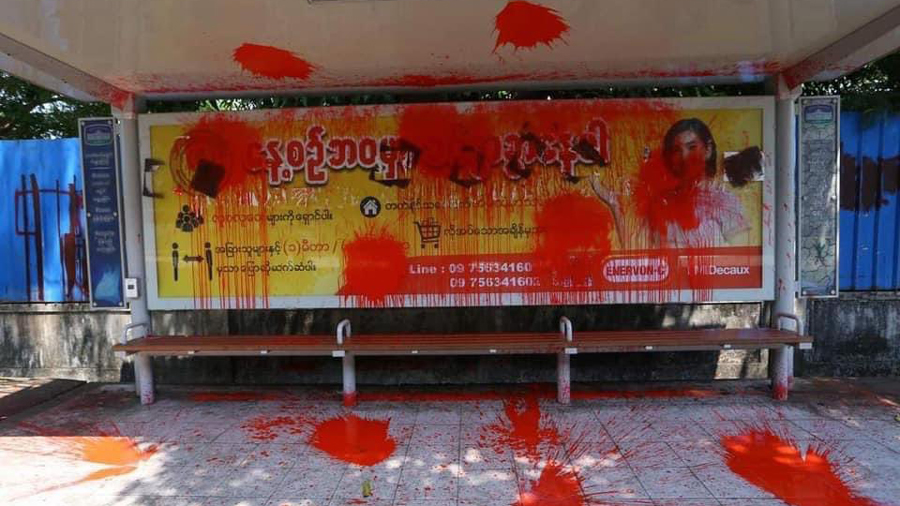 Myanmar youth splash a bus stop with red paint.