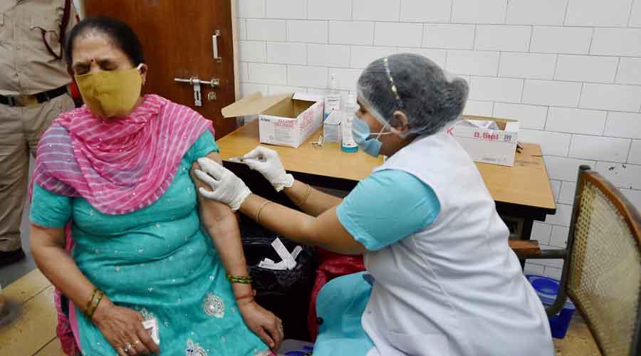 A medic prepares to administer a dose of Covid-19 vaccine in New Delhi