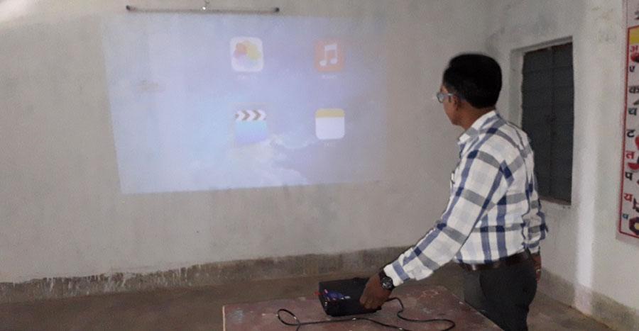Niraj Kumar Mishra using a projector in a class room.