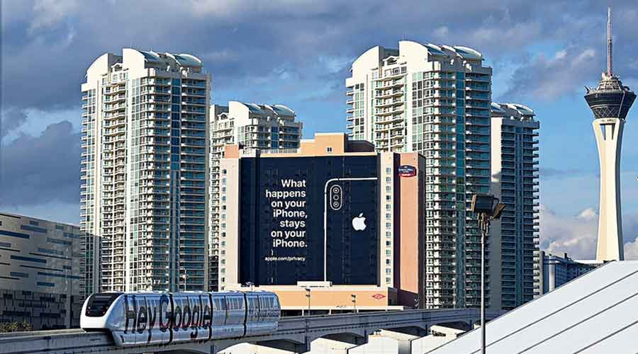 A file picture of a monorail train displaying Google signage moving past a billboard advertising iPhone security during the 2019 Consumer Electronics Show