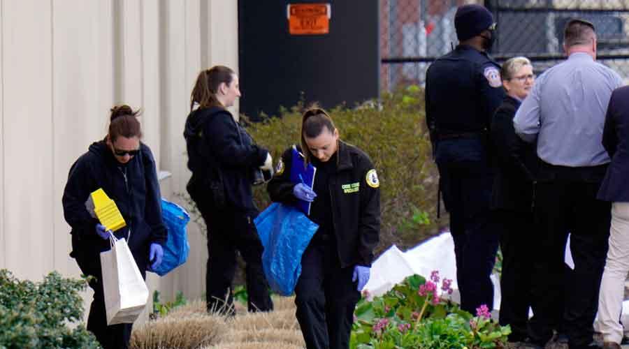 Crime scene technicians investigate the scene at a Fedex facility in Indianapolis