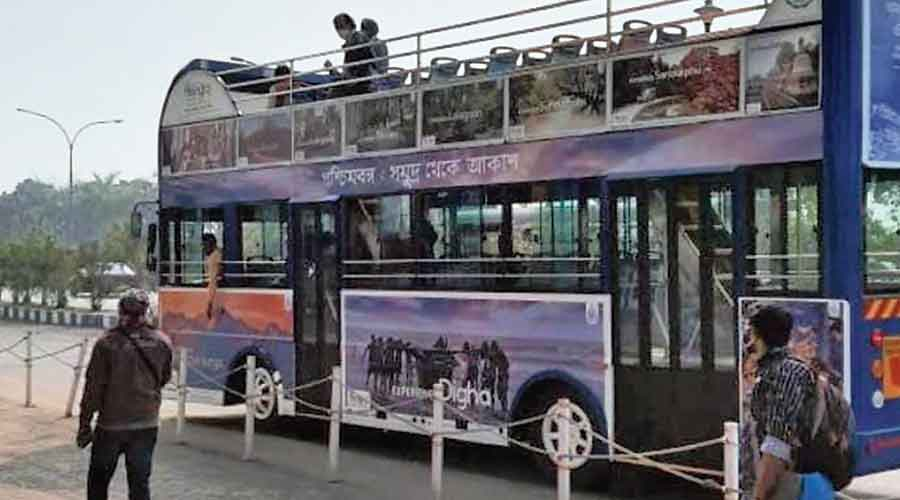 A double-decker bus with an open-air deck on a trial run in New Town
