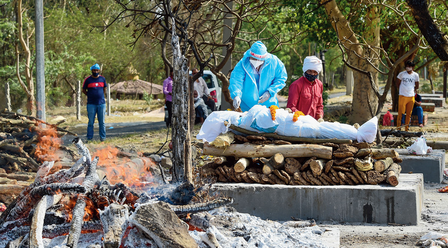 A man wearing PPE performs the last rites of his mother who died of coronavirus at the Ghaziabad Cremation Ground in Ghaziabad district of Uttar Pradesh on Monday.