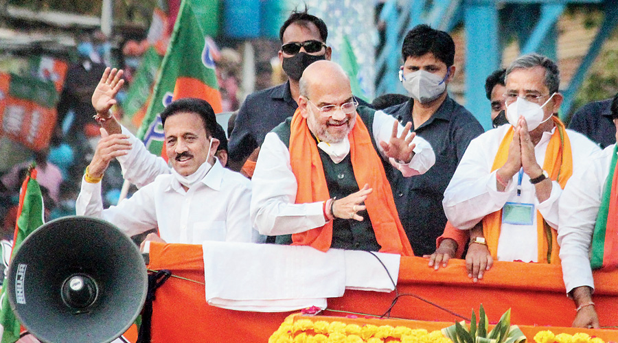 """The picture shows Amit Shah, whose supporters call him the modern Chanakya, during a road show in South Dinajpur, Bengal, on Monday. Yes, the white object hanging below the minister's chin is a mask. On Friday, the Election Commission had said it had taken a """"serious view against repeated violations""""  of the Covid protocol by star campaigners and political leaders who """"expose themselves as well as the public to the danger of infection""""."""