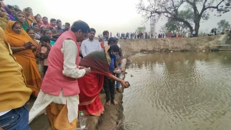 Villagers perform a puja at the pond in Koderma after NHAI takes out waste from it on Tuesday.