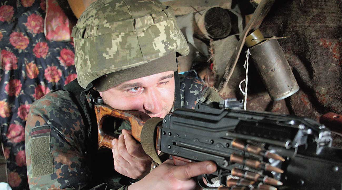 A Ukrainian soldier aims his gun at fighting positions near the rebel-controlled city of Donetsk