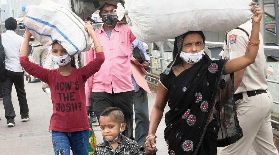 Migrants prepare to board buses out of Delhi on Tuesday.