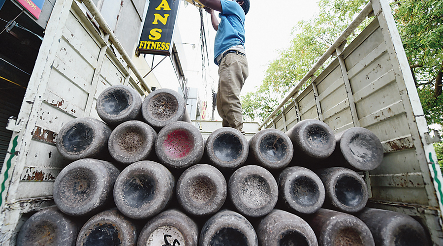 Workers load empty cylinders of medical oxygen in New Delhi on Wednesday.