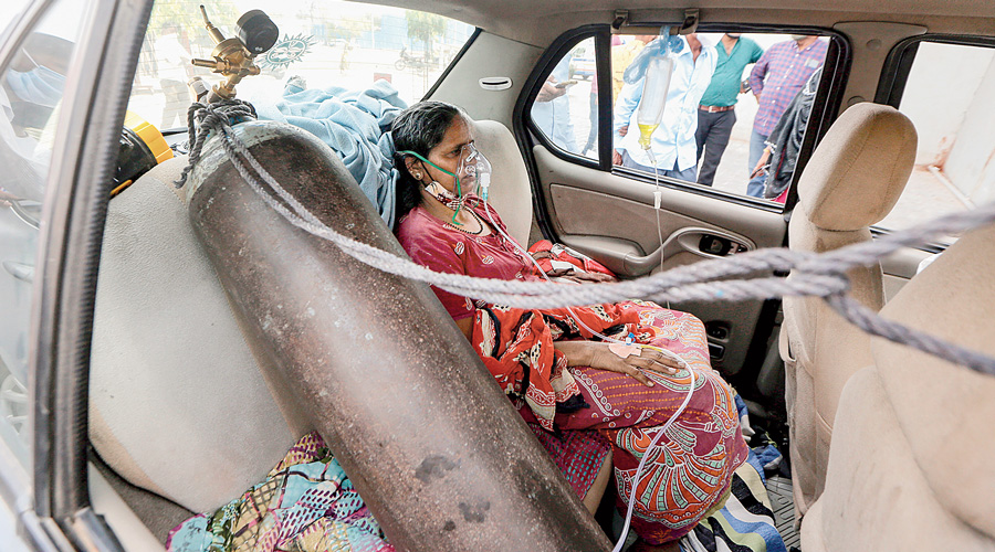 A Covid-19 positive patient gets primary treatment inside a car as she waits to be admited  in hospital in Ahmedabad on Thursday.