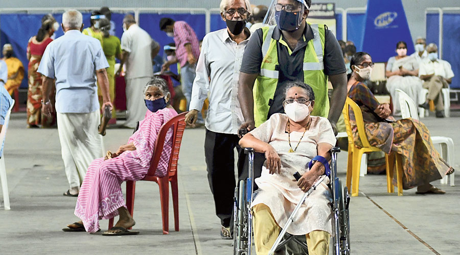 A health worker escorts an elderly woman who is to  receive a dose of Covid-19 vaccine in Thiruvananthapuram on Friday.