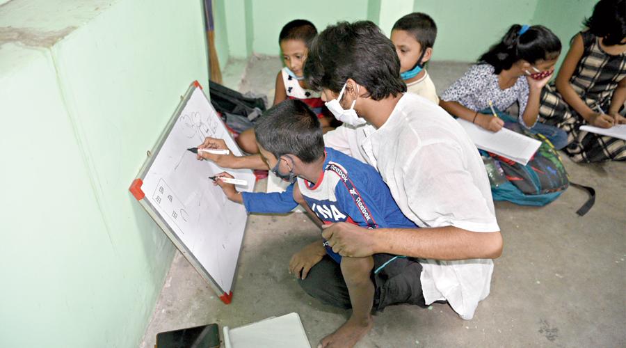 Debjan Sengupta helps a child draw on a board at the school.