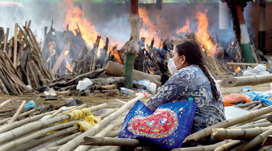 A woman watches the pyres burn at the Ghazipur crematorium in  New Delhi on Monday.