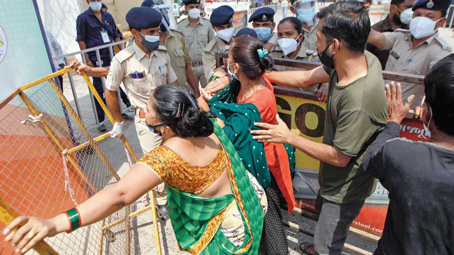 """Relatives of a Covid patient breach barricades in an attempt to enter the Dhanvantri Covid-19 hospital in Ahmedabad for admission on Thursday. Gujarat High Court has directed the state government to make sure each and every patient reaching a designated Covid hospital is attended to and given preliminary treatment even if beds are not available. The bench expressed concern over government-run and designated Covid hospitals in Ahmedabad attending only to patients coming in the EMRI (Emergency Management and Research Institute)-run '108 ambulances' and ignoring those brought in private vehicles. """"The state government and the Ahmedabad Municipal Corporation were aware that there is a shortage of 108 ambulances and if that was so, what justification can there be if patients reach the hospital in their privately arranged vehicles?"""" the court said."""