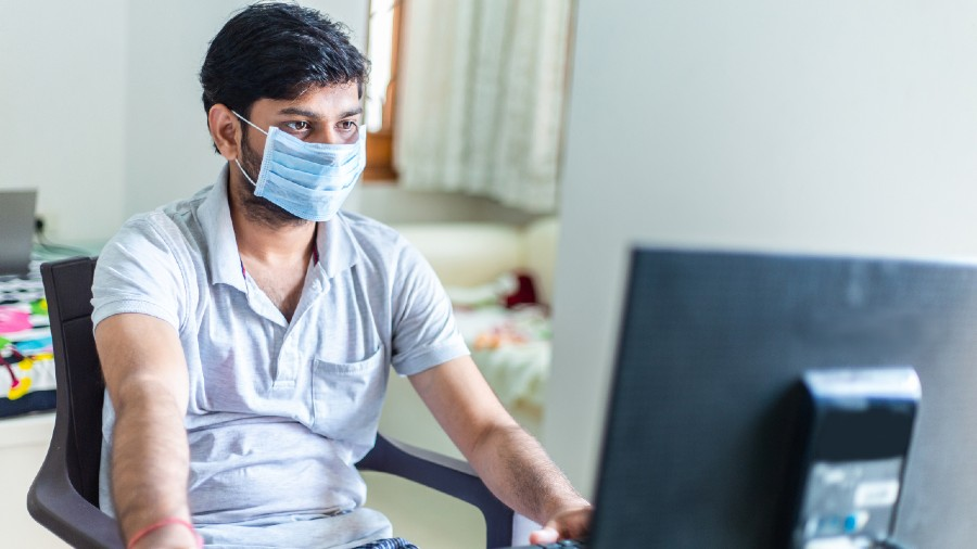 A man with protective medical mask using computer during home isolation