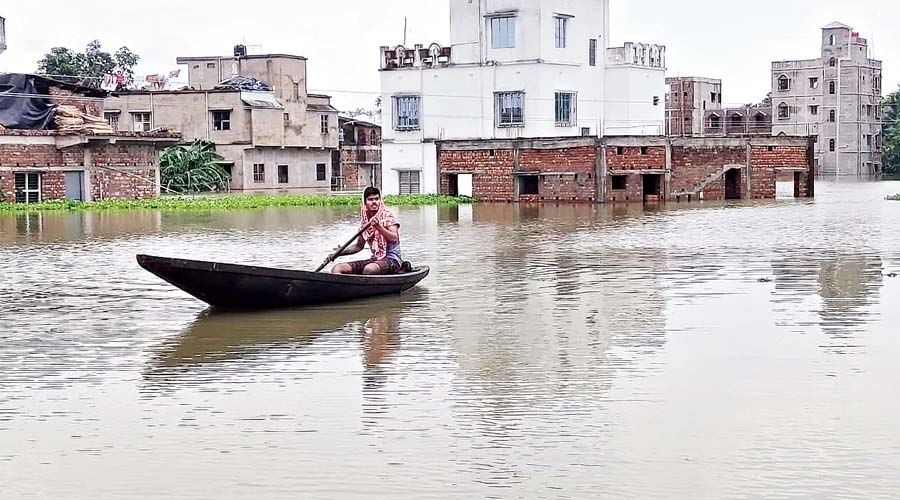 A resident of flood-hit Khanakul's Ghoradaha village in Hooghly district rows a boat on Wednesday.