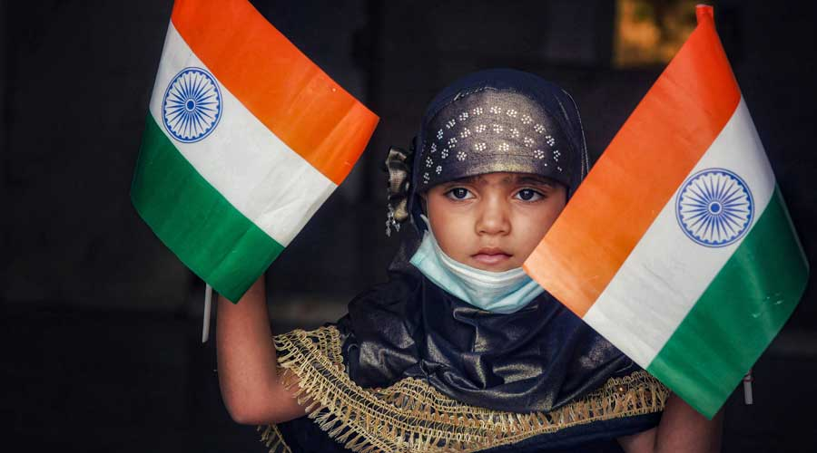 A child waves the national flags to celebrate the 75th Independence Day, in Ajmer