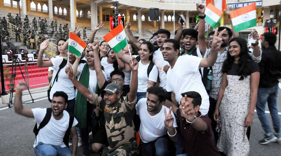Visitors pose with the national flags during a ceremony on the occasion of 75th Independence Day, at the Attari-Wagha border