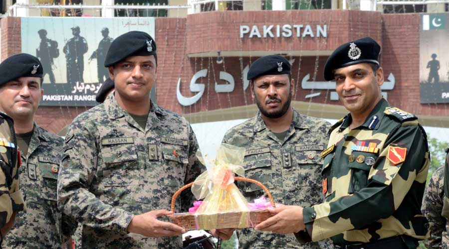 Border Security Force (BSF) Commandant Jasbir Singh presents sweets to Pakistani Wing Commander Hassan on occasion of Indias 75th Independence Day, at the India-Pakistan Attari-Wagah