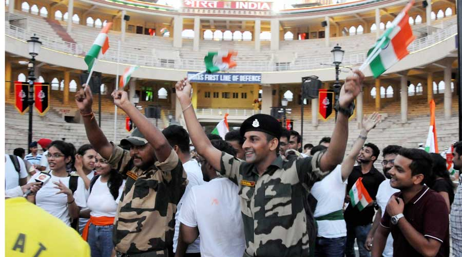 Visitors wave the national flags during a ceremony on the occasion of 75th Independence Day, at the Attari-Wagha border