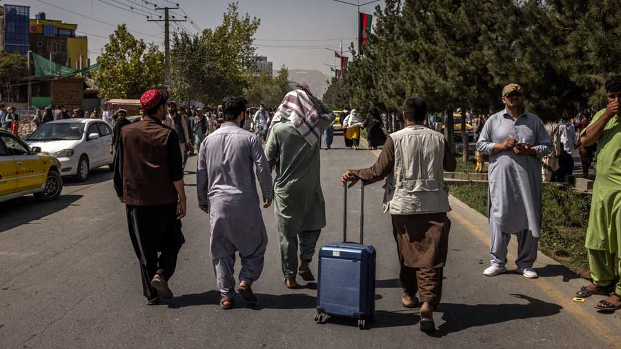 People walk away from the international airport in Kabul, Afghanistan after being denied access on Monday, Aug. 16, 2021, after the Taliban took control of the country.