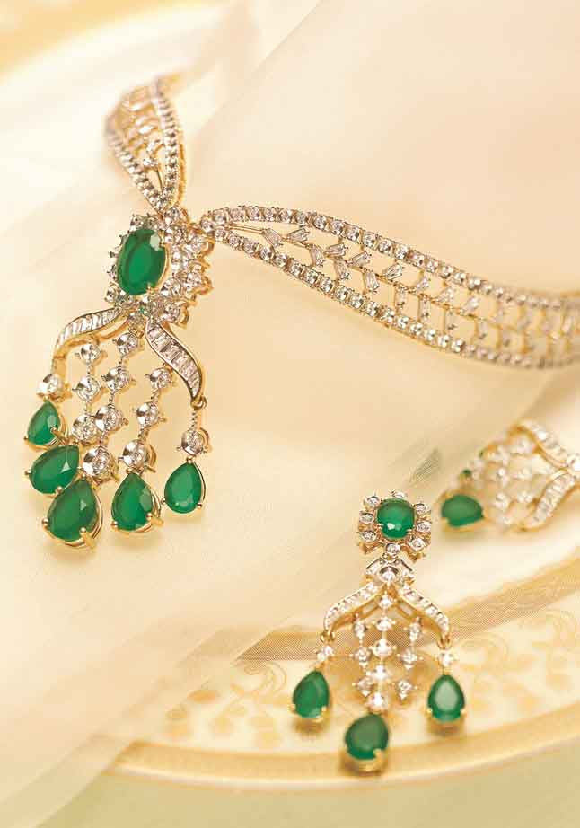 This gold necklace and earring set studded with diamonds and coloured stones can be paired with a lavish gown for the cocktail party. Price on request @Tanishq.