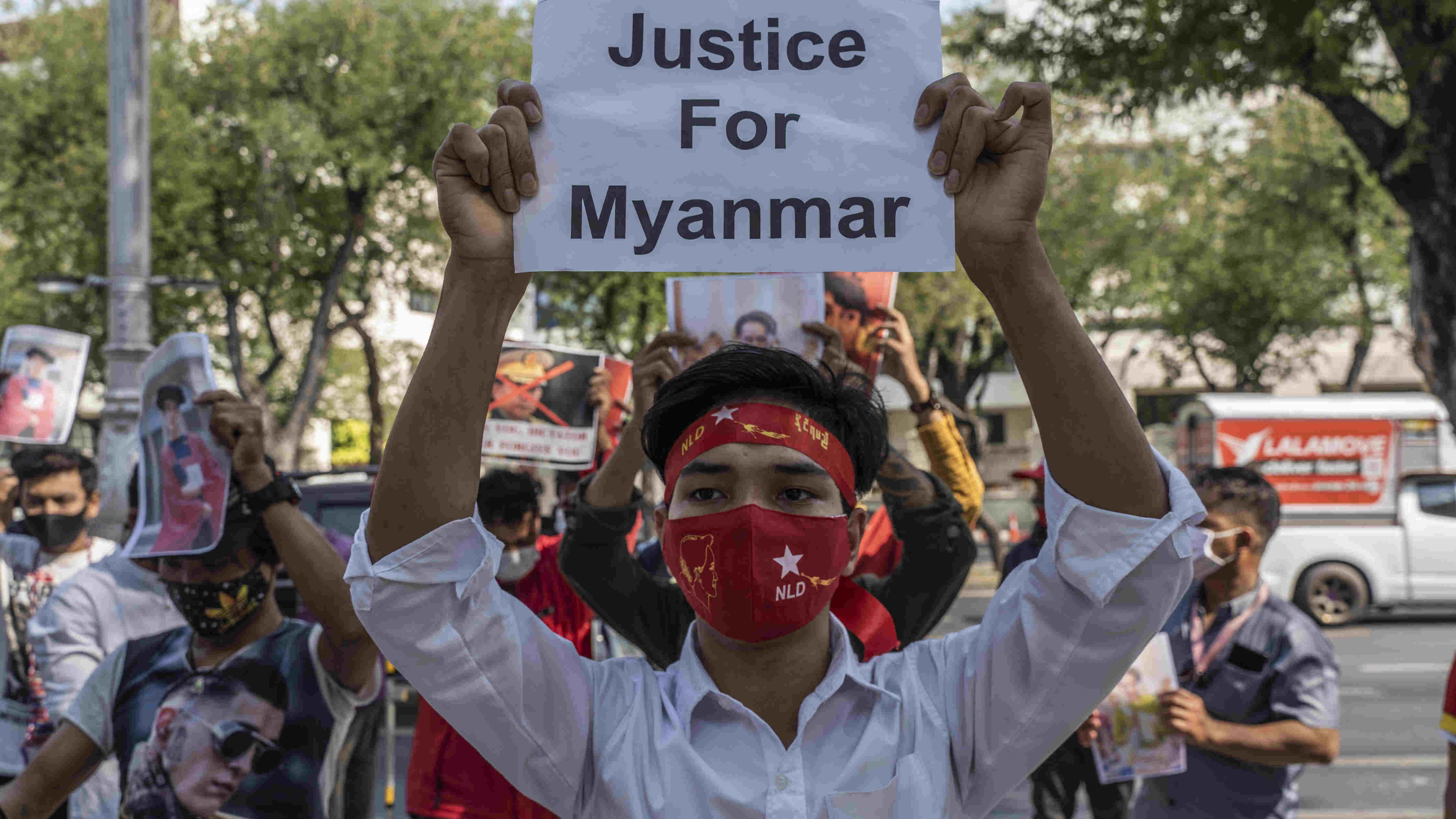 A person wearing a National League for Democracy (NLD) face mask and headband holds a signs during a demonstration outside the United Nations headquarters in Bangkok on Wednesday, Feb. 3, 2021, protesting the recent military coup in Myanmar.