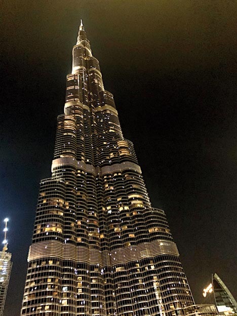 Burj Khalifa stands tall with twinkling lights in the evening.