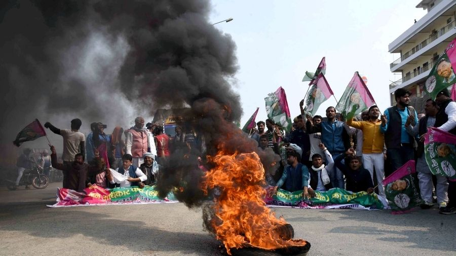Jan Adhikar Party workers burn a tyre, block NH-30 during the 'chakka jam' protest in Patna, on Saturday.