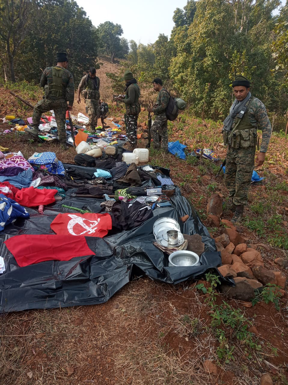 Paramilitary forces look at materials, including ammunition and IEDs,  left by the naxals near the encounter spot in West Singhbhum on Sunday.